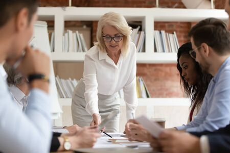 Focused diverse business executive team people with old middle aged boss manager discuss paperwork at group meeting, senior mature female leader presenting financial report work plan at briefing