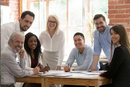 Profesjonalny zespół biznesowy młodzi i starzy ludzie pozują razem przy biurowym stole, szczęśliwi zróżnicowani przywódcy pracownicy patrzący na kamerę, uśmiechający się wielorasowy personel ludzie korporacyjni pracownicy portret grupowy