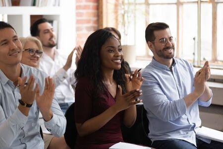 Multirassische glückliche afrikanische und kaukasische Geschäftsteam-Publikumsleute applaudieren für die Workshop-Präsentation, verschiedene Zuhörergruppen sitzen auf Stühlen und klatschen beim Seminar der Unternehmensschulungskonferenz in die Hand