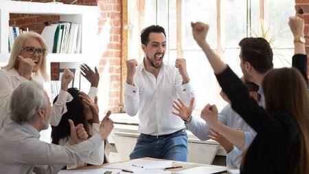 El equipo de negocios emocionado eufórico celebra la victoria corporativa juntos en la oficina, el grupo de profesionales llenos de alegría se regocijan en la victoria de la empresa, el éxito del trabajo en equipo gana el concepto de triunfo en la mesa de conferencias Foto de archivo
