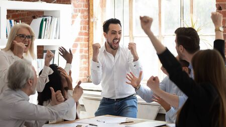 Euphoric excited business team celebrate corporate victory together in office, happy overjoyed professionals group rejoice company victory, teamwork success win triumph concept at conference table