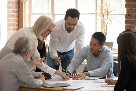 Diverse business project team young and old workers brainstorm on paperwork talk engaged in teamwork at corporate briefing, serious staff people discuss work plan pointing at papers at group meeting