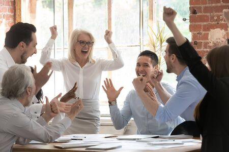 Overjoyed happy corporate business team people scream celebrate triumph reward together at meeting, excited executives group motivated by victory win good result engaged in teamwork success concept