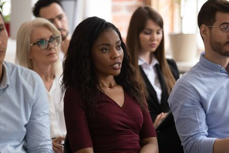 Serious black female professional ask question at group seminar lecture event, confident african business woman training conference participant sit on chair talking at corporate meeting workshop