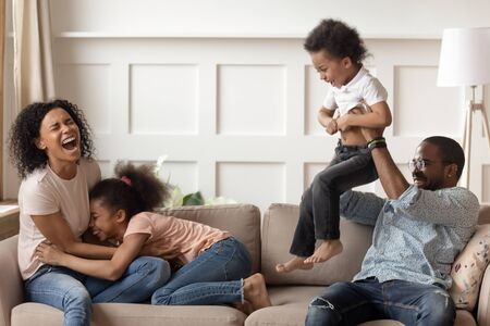 Happy black family having fun laughing with children, cheerful african american parents tickling lifting mixed race kids enjoy weekend on couch, mom dad with little son daughter playing at home 스톡 콘텐츠 - 126760635