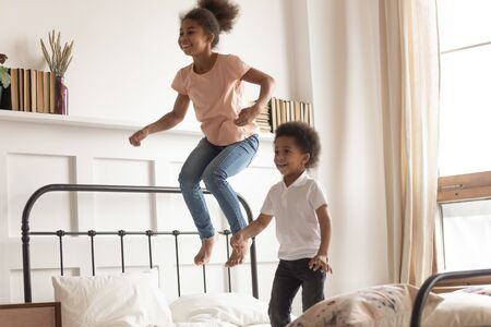 Happy cute active little african american kids boy and girl jumping on bed laughing together, two funny small energetic mixed race children brother with sister having fun play active game in bedroom