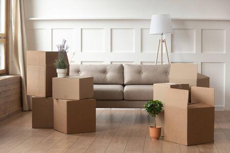 Concetto di giorno in movimento, scatole di cartone impilate con oggetti domestici nel soggiorno di una casa moderna, contenitori imballati sul pavimento nella nuova casa, trasferimento, ristrutturazione, trasloco e servizio di consegna