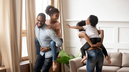 Happy african family mom and dad piggyback little children laugh play in living room, smiling black parents carrying cute kids on back having fun enjoy leisure active game together feel joy at home