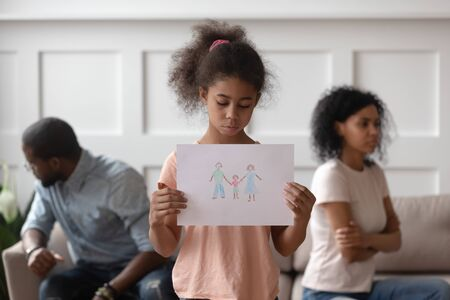 Sad african american school child girl holding family picture drawing feeling upset about parents divorce, innocent sensitive little kid suffer from trauma offended by fights conflicts shared custody Stock Photo