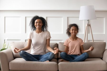 Smiling calm african family healthy mom teaching yoga cute little kid daughter doing exercises sit on sofa in lotus pose, happy mindful mixed race mother and child girl meditating together at home