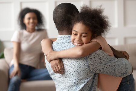Happy cute little african american kid daughter embracing black dad at home, funny small mixed race child and father hugging cuddling, daddy and child love connection, family reunion, joint custody