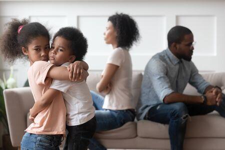 Trieste kleine afro-amerikaanse kinderen omarmen voelen zich gekwetst boos over ouders vechten thuis, gestrest overstuur kinderen zoon dochter lijdt aan psychologisch trauma probleem familie conflict scheidingsconcept