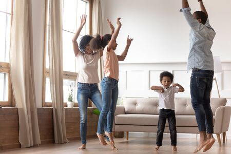Joyful happy african family having fun jumping in living room together, active black parents and little cute kids dancing at home, mixed race mom dad with small kids laughing enjoy leisure activity