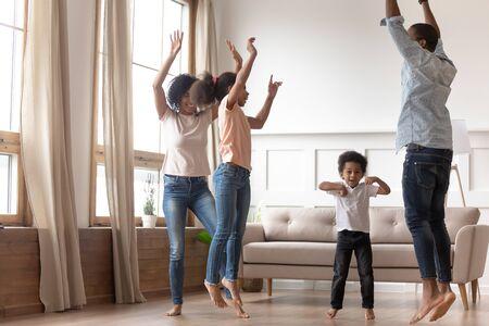 Vrolijke gelukkige Afrikaanse familie plezier samen springen in de woonkamer, actieve zwarte ouders en kleine schattige kinderen dansen thuis, gemengd ras moeder vader met kleine kinderen lachen genieten van vrijetijdsbesteding