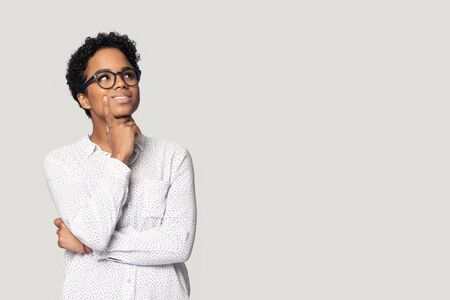 Thoughtful african American girl in glasses isolated on grey studio background look up at blank copy space aside, pensive biracial millennial woman think pondering over sale offer making choice