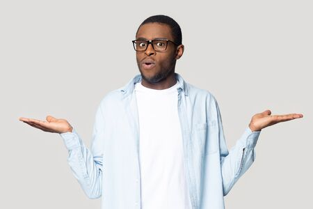Doubtful african American millennial male in glasses isolated on grey studio background compare offers or prices, unsure black man keep hands aside doubt over deal, make decision or choice
