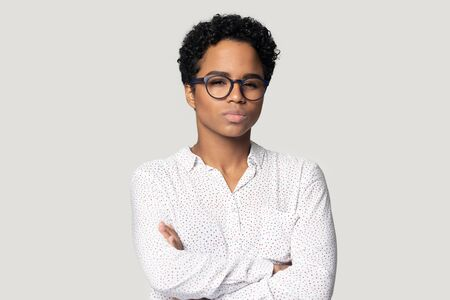 Thoughtful unsure african American young woman in glasses isolated on grey studio background look at camera, pensive biracial girl feel hesitant doubtful thinking over problem stand with arms crossed Standard-Bild