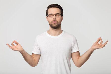 Kaukasischer junger Mann mit Brille, weißem T-Shirt, isoliert auf grauem Studiohintergrund, faltende Finger, Atemübungen zum Stressabbau, Verbesserung der Selbstkontrolle, Yoga Standard-Bild