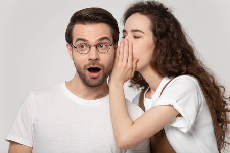 Girlfriend whispering in ear to boyfriend a secret, millennial couple gossiping posing isolated on grey studio background, guy open mouth makes big eyes feels shocked surprised hearing latest rumors