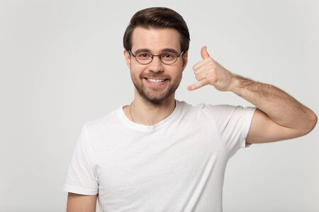 Pretty millennial man wearing glasses white t-shirt look at camera showing call me back body language gesture with hand posing isolated on gray studio background, eyewear sale store make offer concept Stock fotó