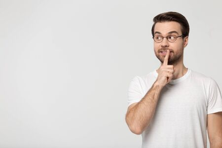 Man wearing glasses white t-shirt holding finger at lips showing be quiet gesture symbol standing aside isolated on grey studio background look at copy space concept image of secret hidden information. Banque d'images - 127408387