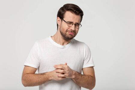 Man wearing glasses white t-shirt closed eyes being under pressure stress screaming or whines standing isolated on grey studio background, nagging man feeling desperate, loser unhappy person concept