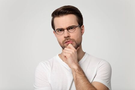 Frowning man wearing glasses white t-shirt holding hand on chin looking at camera feels distrustful studio head shot portrait isolated on grey background, concept of distrust chary suspicious person