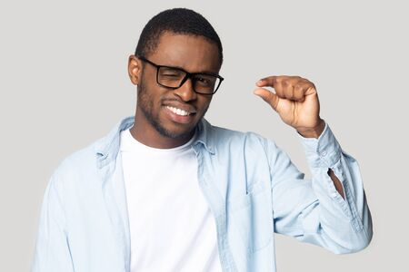 Smiling millennial african American male in glasses isolated on grey studio background show small prices with finger gesture, happy black man look at camera use hand demonstrate little measurement