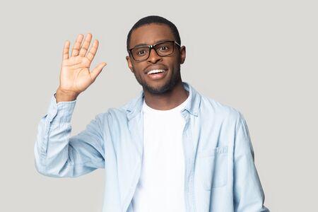 Souriant homme afro-américain du millénaire dans des verres isolé sur fond gris studio vague main, homme noir heureux dans des lunettes regarde la caméra dire bonjour salutation avec le public ou les abonnés Banque d'images