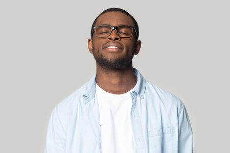 Calm african American man in glasses and casual wear stand with eyes closed dreaming or visualizing, peaceful black male in spectacles take break meditating controlling emotions. Stress free concept 写真素材