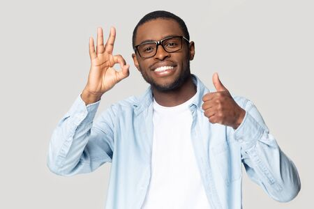 Happy african American male in glasses look at camera show thumb up all right sign satisfied with service, smiling black man in spectacles isolated on grey studio background excited recommend offer Stock Photo