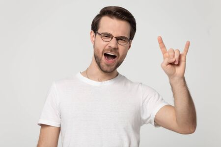 Cheerful 30s man wearing glasses white t-shirt looking at camera raises pinky and index fingers showing rock and roll hand heavy metal, devil horns hand sign gesture isolated on grey studio background