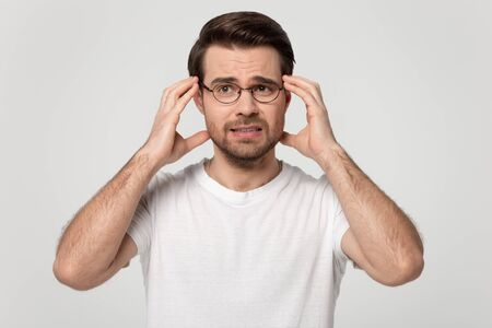 Anxious millennial man wearing glasses white t-shirt touching head temples experiencing stress having troubles difficulties to resolve issues, panic attack posing isolated on grey studio background Stok Fotoğraf
