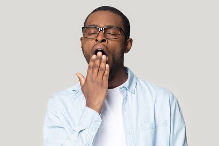 Exhausted millennial african American man in glasses isolated on grey studio background sigh having sleep deprivation, tired black male in spectacles yawn cover mouth feel sleepy, lack rest or relax