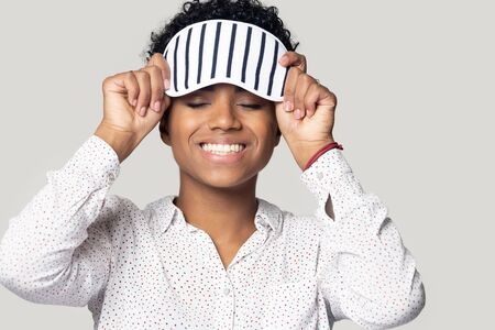 Smiling african American millennial woman isolated on grey studio background wear sleeping stripy eye mask, happy biracial young girl with sleepwear accessory on head feel healthy refreshed after nap