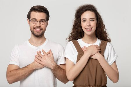 Grateful millennial couple looking at camera holding hands on chest feeling thankful pose isolated on gray studio background expressing heartfelt love appreciation gratitude and goodness concept image. Stock Photo