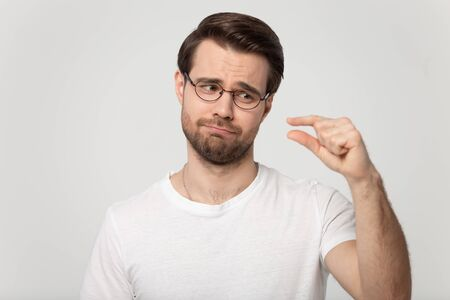 Head shot portrait guy isolated on grey background wearing glasses look at hand showing with fingers something small feels disappointed pity about little size insufficient length or thickness concept. 免版税图像
