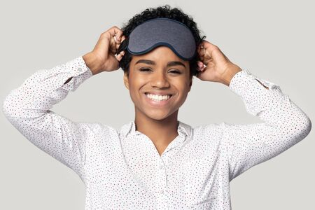 Happy african American millennial woman isolated on grey studio background wearing sleepwear accessory on head, smiling black biracial girl with gray sleeping mask look at camera feel refreshed Imagens