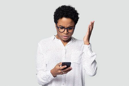Confused african American millennial woman isolated on grey studio background hold smartphone have problem with gadget, frustrated biracial female experience cellphone malfunction or virus attack
