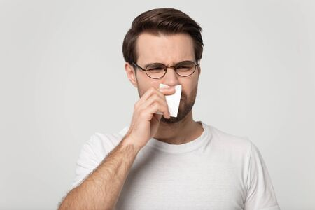 Sick unhealthy young man holding handkerchief paper tissue sneezing wiping blowing runny nose, suffers from unpleasant smell on grey background head shot, concept of seasonal allergy or awful scent