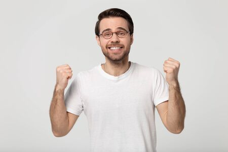 Happy man wearing glasses white t-shirt look at camera clenched fists enjoy moment of success excited by good news, lucky successful winner celebrating great result isolated on grey studio background