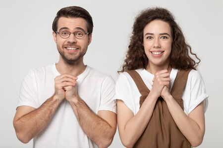Couple full of hope and faith waiting for miracle or realization of cherished dream holds folded palms together near chest look at camera isolated on grey background, gesture of heartfelt anticipation