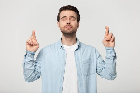 Studio shot millennial guy wearing blue shirt closed eyes making gesture crossing fingers asks for good luck, isolated on grey background, concept of hope superstition believe and let dream come true