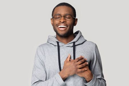 Happy african American man in glasses isolated on grey studio background keep hands at heart chest feel grateful, thankful black male in spectacles stand with eyes closed smiling thanking to god Stock fotó
