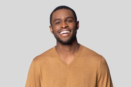 Kopfschussporträt eines lächelnden afroamerikanischen tausendjährigen Mannes im T-Shirt einzeln auf grauem Studiohintergrund, glücklicher schwarzer männlicher Blick in die Kamera fühlt sich zufrieden oder erfreut lachend posiert für Bild Standard-Bild