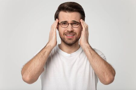 Studio shot headache concept image isolated on grey background millennial 30s man wearing eyeglasses look at camera massaging touching temples suffers from pounding throbbing tension feels discomfort. Imagens