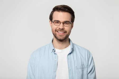 Kopfschussporträt einzeln auf grauem Studiohintergrund attraktiver lächelnder Mann mit Brille blaues Hemd fühlt sich gesund positiv an, wenn er drinnen posiert, Vertreter der tausendjährigen Generation, Optikgeschäft-Anzeigenkonzept