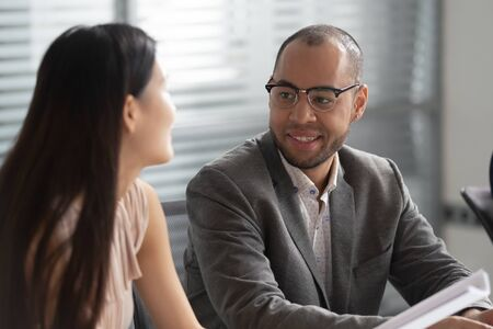 Smiling african american business man talking to asian woman colleague at workplace having pleasant conversation discussion sitting in office, happy diverse coworkers enjoy chatting at work break