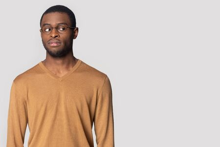 Thoughtful african American millennial man in glasses stand aside look at blank copy space considering offer, pensive black male isolated on grey studio background stare at sale or discount message