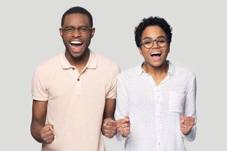 Overjoyed african American man and woman in glasses isolated on grey studio background scream with happiness, excited ethnic couple in spectacles feel euphoric shout loud celebrating win or success Stockfoto